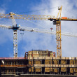 Crane on top of modern building under construction — Stock Photo