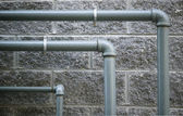 Pipes against grungy stone wall — Stock Photo