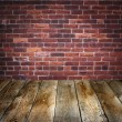 Room with brick wall and wooden floor - Stock Photo