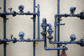 Plumbing pipes on rough wall — Stock Photo
