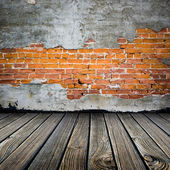 Room with stucco peeling brick wall and wooden floor — Stock Photo