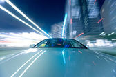 The car moves at great speed at the night. — Stock Photo