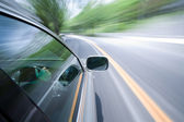 The car moves at great speed at the sunny day. — Stock Photo