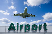 Aeroplane Clouds And Airport sign — Stock Photo