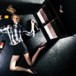 Girl lying on a black floor and next to bottles of alcohol - Stock Photo