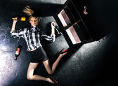 Girl lying on a black floor and next to bottles of alcohol — Stock Photo