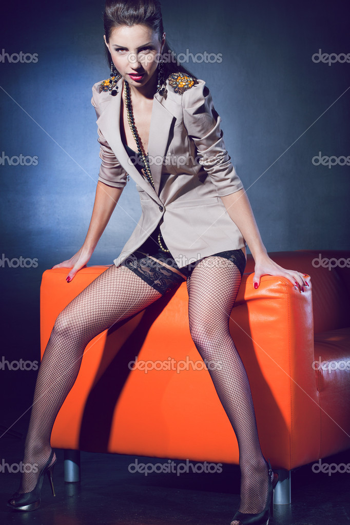 Glamour girl wearing a jacket and stockings on the orange couch — Stock Photo #8687743