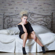 Beautiful sexy girl in black dress sitting on a bed — Stock Photo