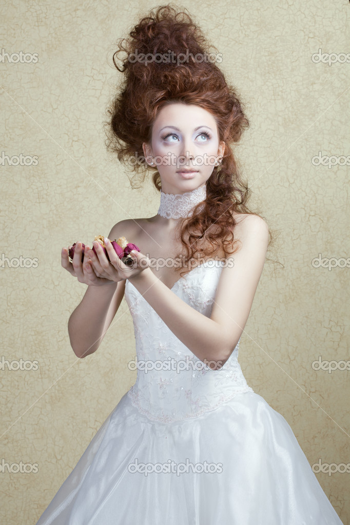 Beautiful girl with an unusual hair style in a white dress with rose petals in the hands of — Photo #8732747