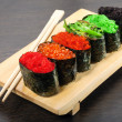 Sushi on wooden plate with sticks — Stock Photo