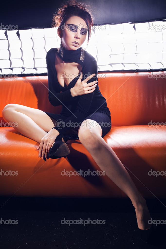 Glamorous girl in the orange couch — Stock Photo #9177736