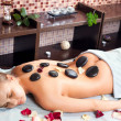 Stock Photo: Glad womreceiving massage with hot stone in spcenter