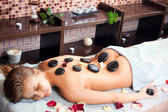 Glad woman receiving a massage with hot stone in a spa center — Stock Photo