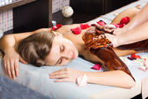 Cacao therapy applied to young woman in a spa — Stock Photo