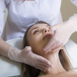 Beautiful young woman receiving facial massage with closed eyes — Stock Photo #9362015