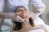 Beautiful young woman receiving facial massage with closed eyes — Stock Photo