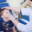 Stock Photo: Medical otitus examination of a child at a ear nose throat docto