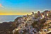 A sunet shinning white buildings in Oia, Santorini, Greece — Stock Photo