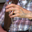 Wineglass in old hands — Stock Photo