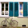 Bicycle parked in front of two windows - Stock Photo