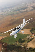 Small airplane flying over farm — Stock Photo
