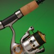 Spinning reel attached to a cork handled fishing pole — Stock Photo #8650955