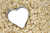 White heart outlined with silver on a bed of oatmeal — Stock Photo