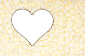 White chocolate morsels surround a silver heart — Stock Photo