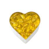Top-down mening van zilveren hart gevuld met zalm olie — Stockfoto