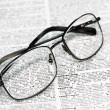 Closeup view of glasses at rest on a dictionary — Stock Photo