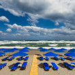 Blue parasols at an empty, stormy beach — Stock Photo
