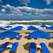 Royalty-Free Stock Photo: Blue parasols at an empty, stormy beach