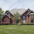 Large brick home in suburbs - Stock Photo