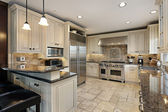 Upscale kitchen with breakfast bar — Stok fotoğraf