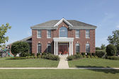 Large brick home with white columns — Stock Photo