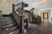 Foyer with dark wood stairway — Stock Photo