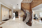 Foyer in luxury home with curved staircase — Stock Photo