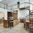 Stock Photo: Large kitchen with spiral stairway to second floor