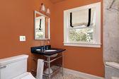 Powder room with orange walls — Stockfoto
