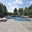 Swimming pool with large stone patio - Stock Photo
