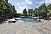 Swimming pool with large stone patio — Stock Photo