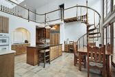 Amplia cocina con escalera espiral al segundo piso — Foto de Stock