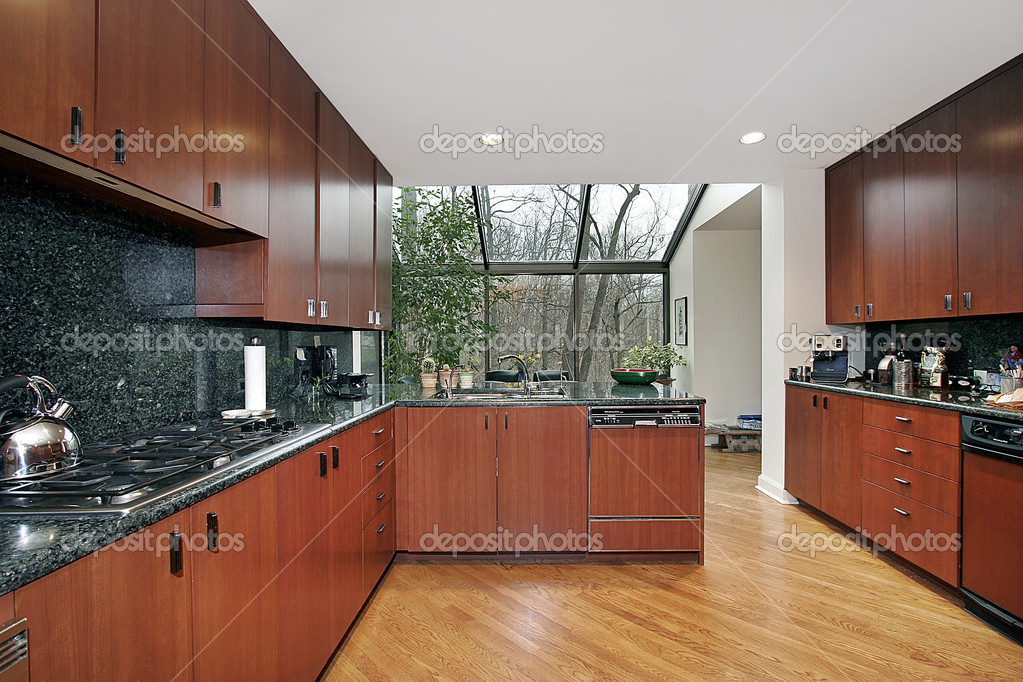Wood paneled kitchen with glass enclosed eating area  Stock Photo #8716726