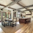 Kitchen with island and ceiling wood beams - Photo