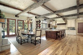 Kitchen with island and ceiling wood beams — Stock Photo