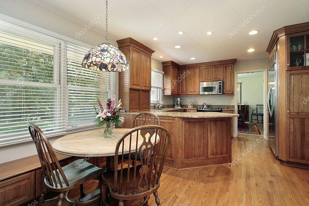 Wood cabinet kitchen with eating area and windows — Stock Photo #8727756