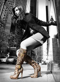 Sexy girl in leopard boots posing in the street — Stock Photo