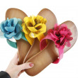 Colored flip-flops with flowers in hand — Stock Photo