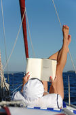 Young woman reading and sunbathing on sail boat — Stock Photo