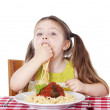 Beautiful girl eating pasta and meatballs with hands — Stock Photo #10717683